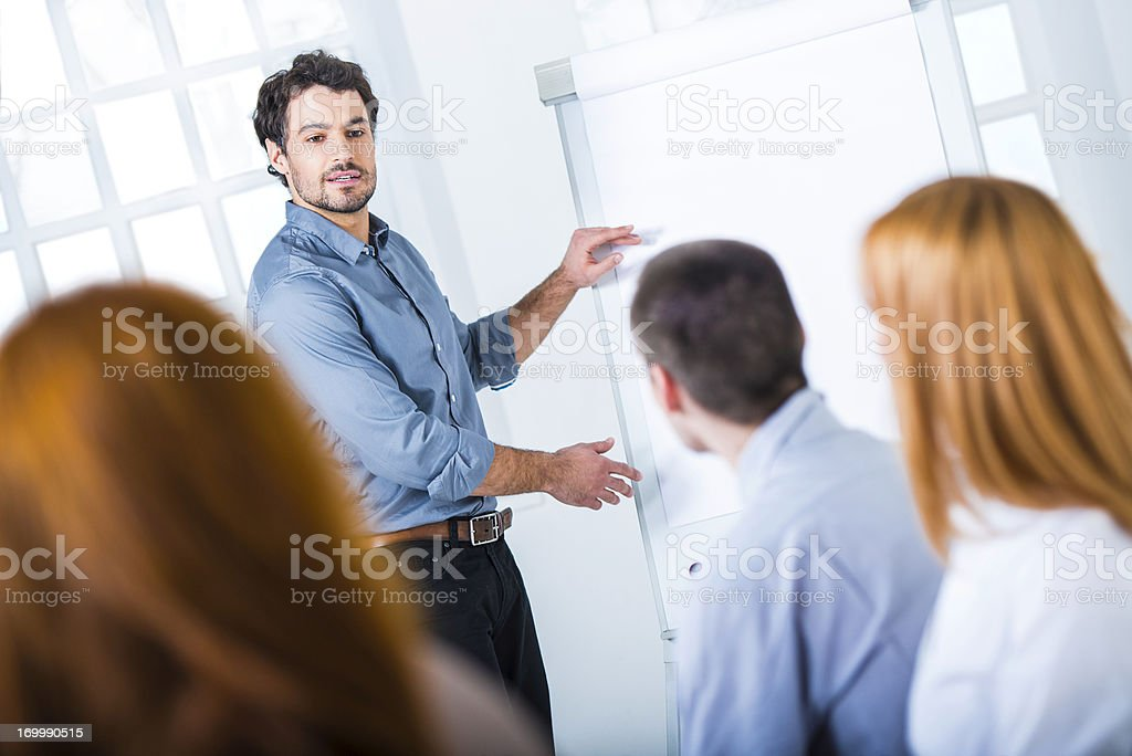 Young Businessman Presenting His Ideas on Flip Chart to Colleagues stock photo