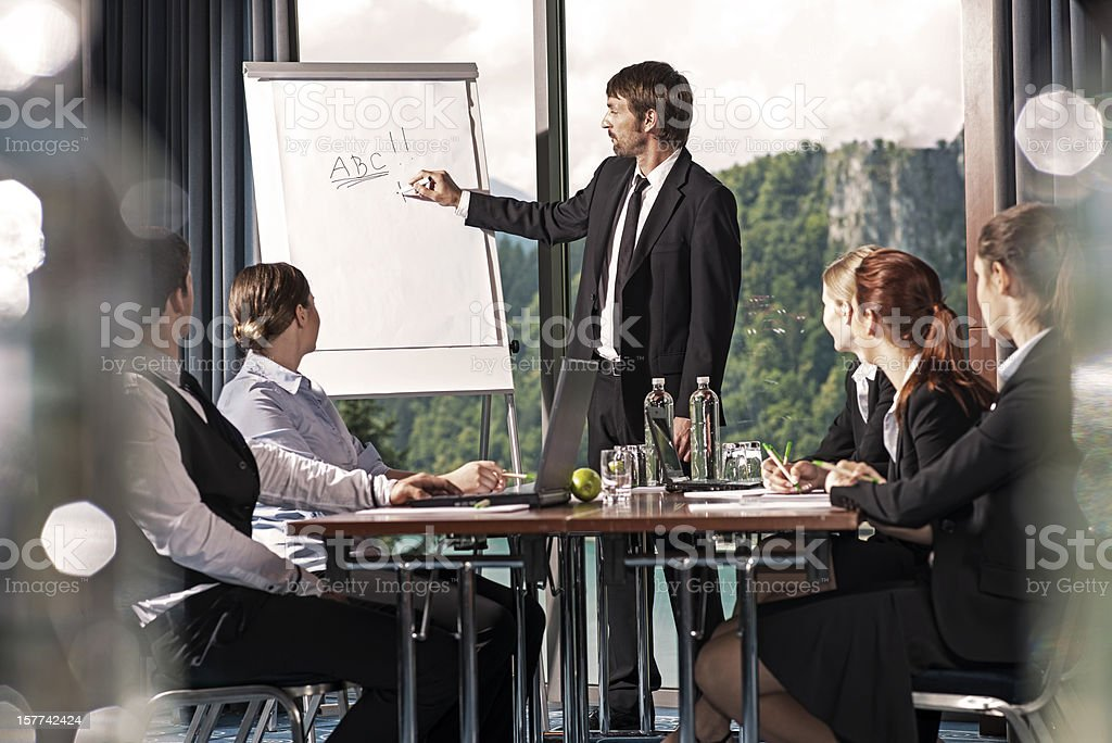 Young businessman presenting his ideas on whiteboard to colleagues royalty-free stock photo