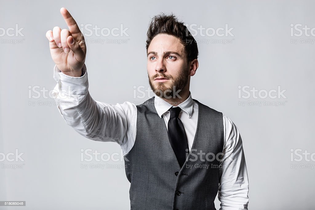 Young businessman pressing a button on an imaginary screen. stock photo