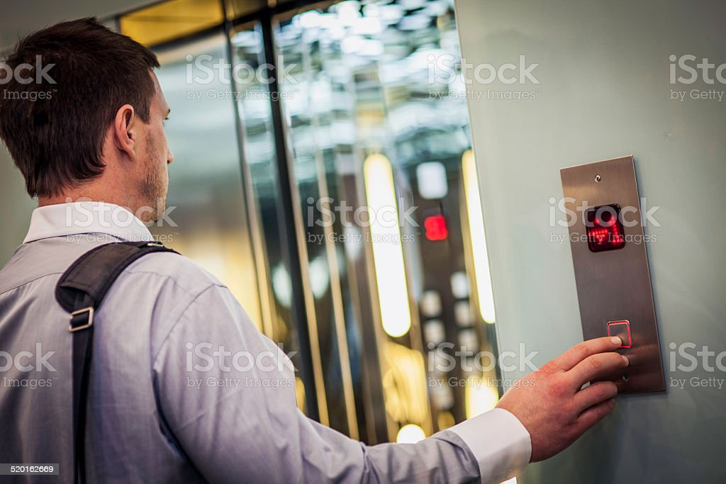 Young Businessman Pushing Buttons on an Elevator stock photo