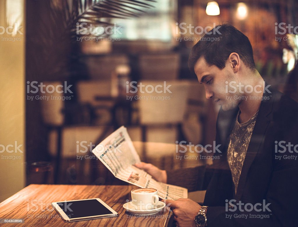 young businessman reading a newspaper stock photo