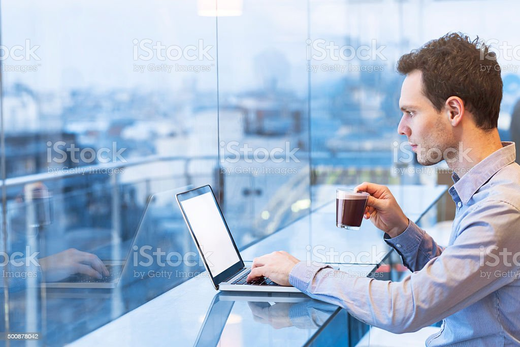 Young businessman reading emails on laptop in modern coffee shop stock photo
