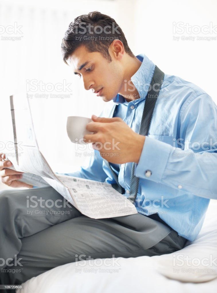 Young businessman reading newspaper while having coffee royalty-free stock photo