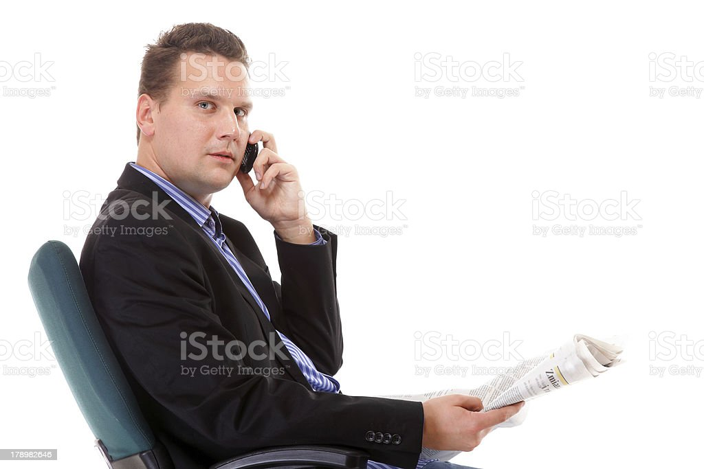 young businessman reads newspaper while phoning royalty-free stock photo