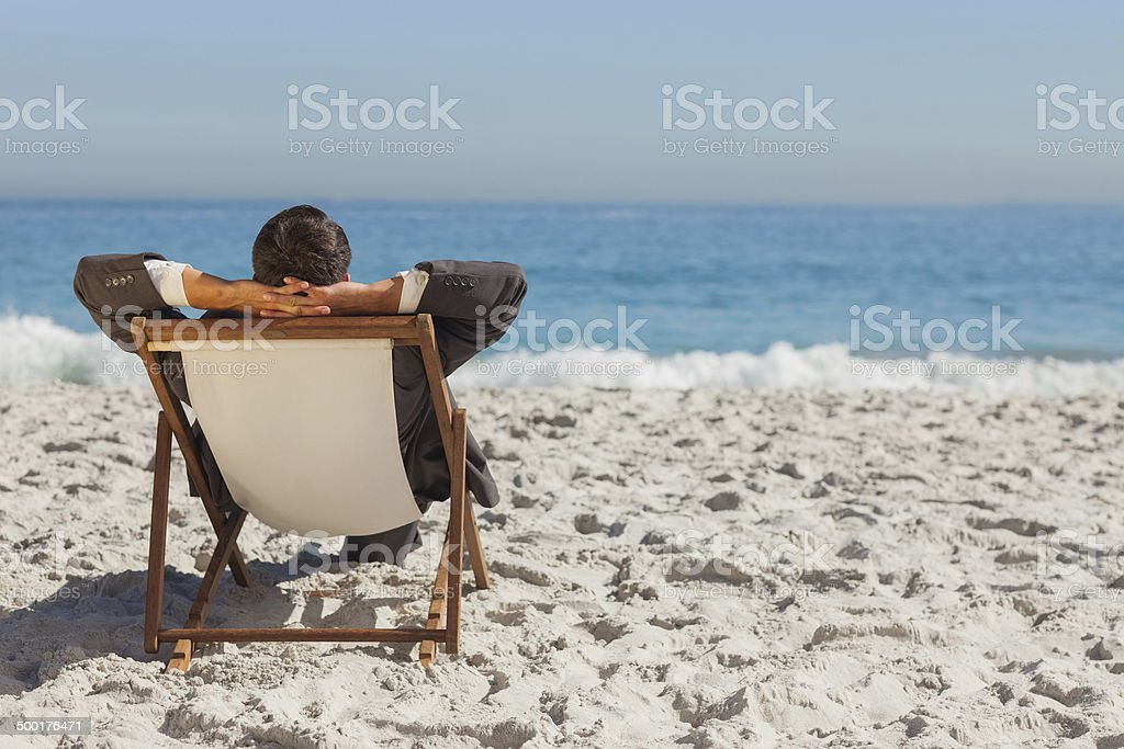 Young businessman relaxing on his sun lounger stock photo