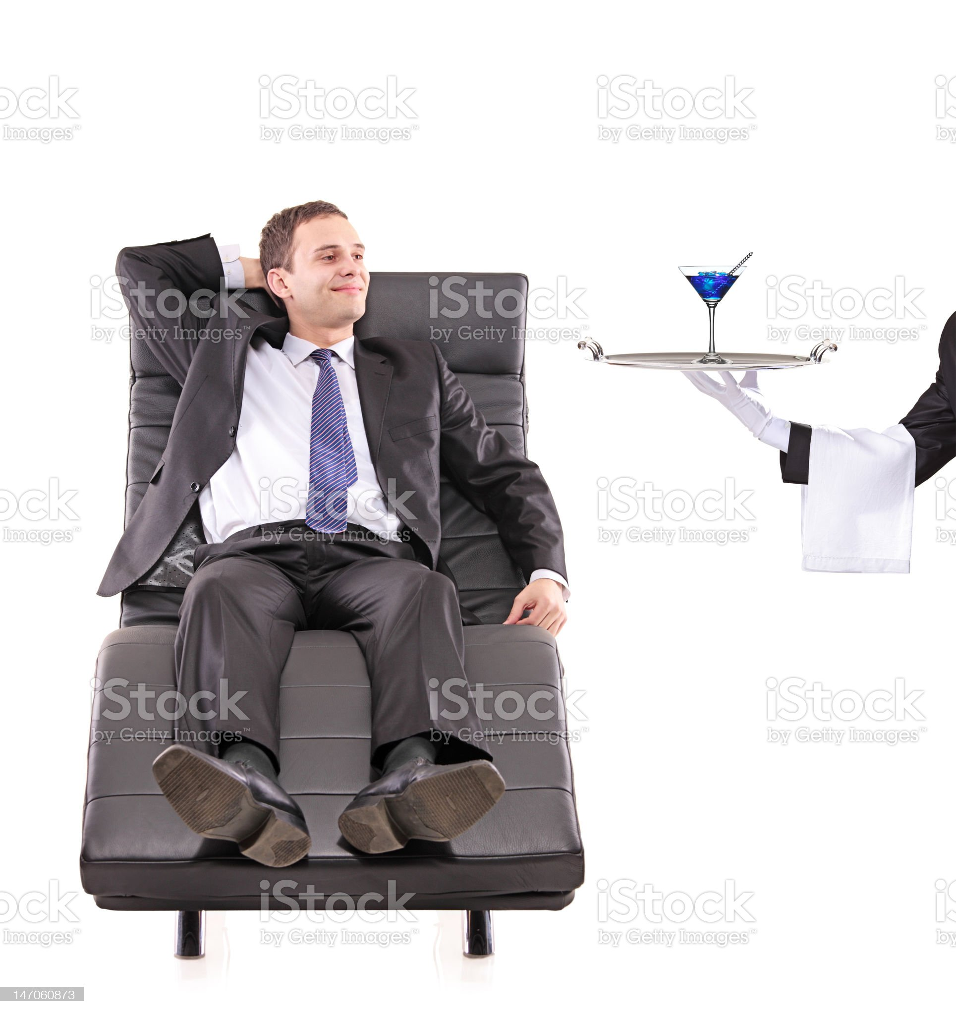 Young businessman relaxing while the butler serving a cocktail royalty-free stock photo