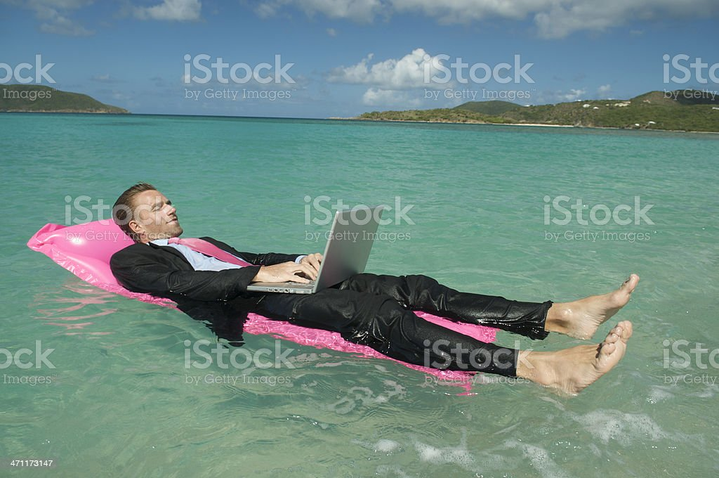 Young Businessman Relaxing with Laptop Working Floating in Tropical Water royalty-free stock photo