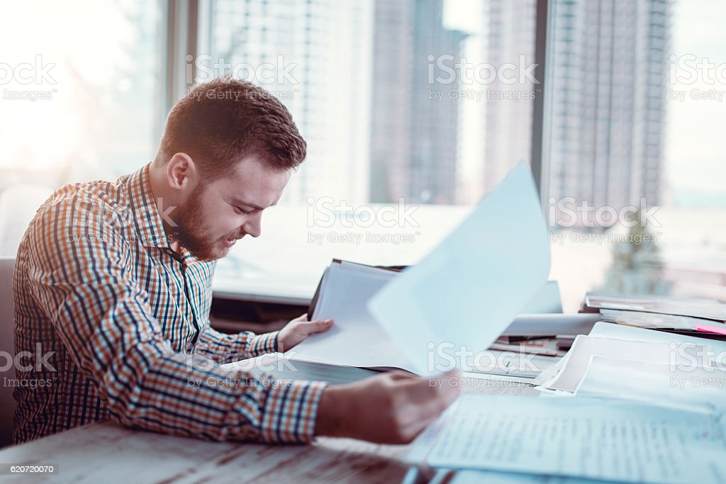Young Businessman Reviewing Plans at Blue Prints on Desk stock photo