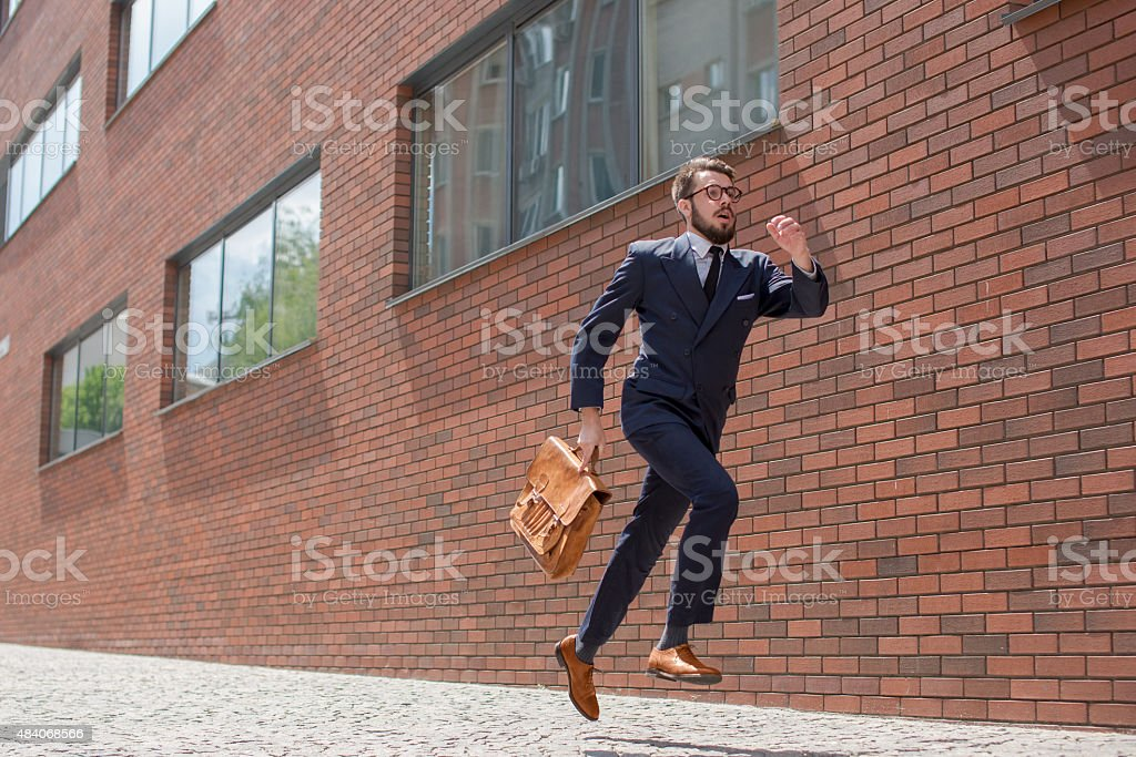 young businessman running in a city street stock photo