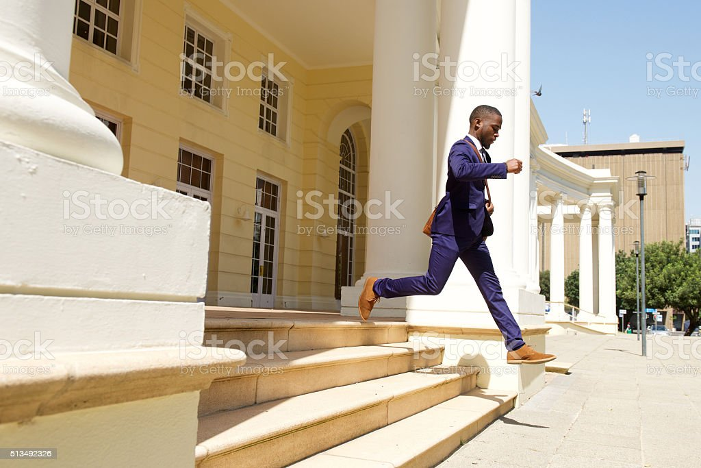 Young businessman running out of a building stock photo