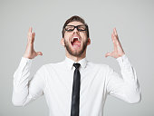Young businessman screaming - isolated on gray background.