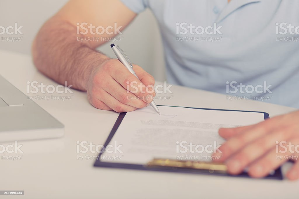 Young businessman signs a contract, toned stock photo