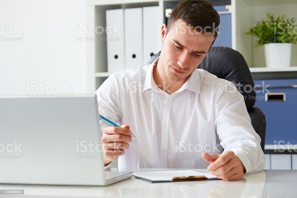 Young businessman signs a document stock photo