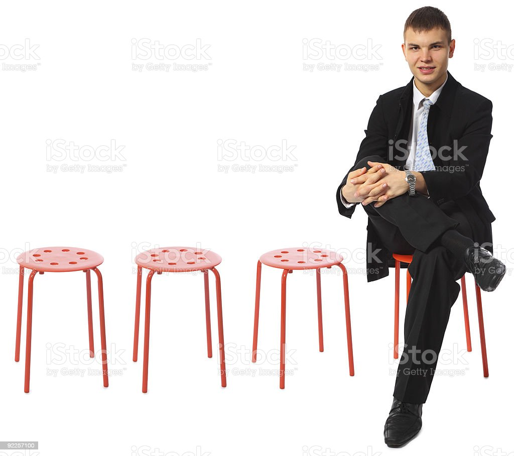 young businessman sits on red stool stock photo