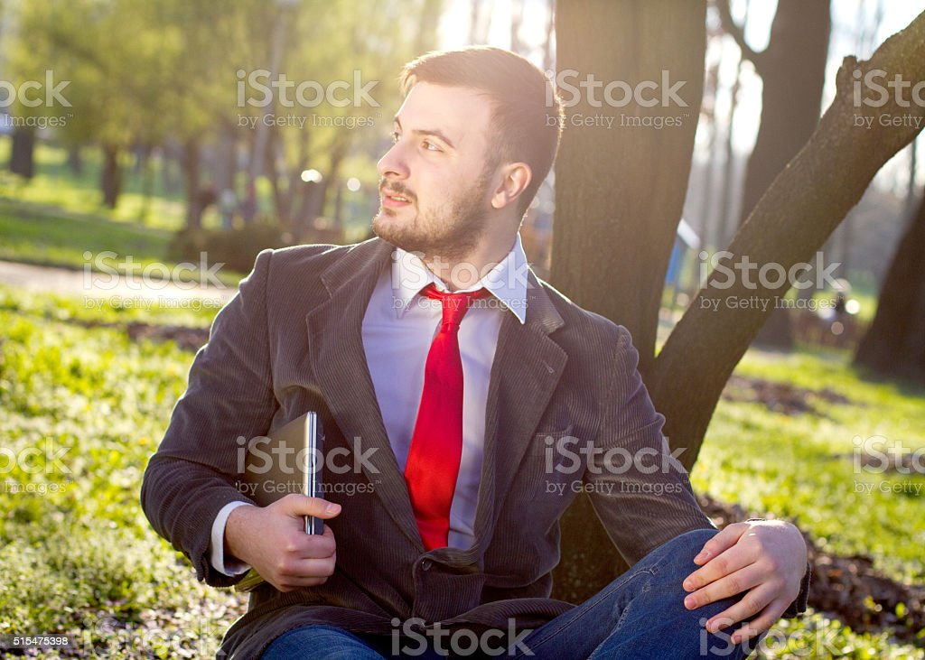 Young businessman sitting in the park stock photo
