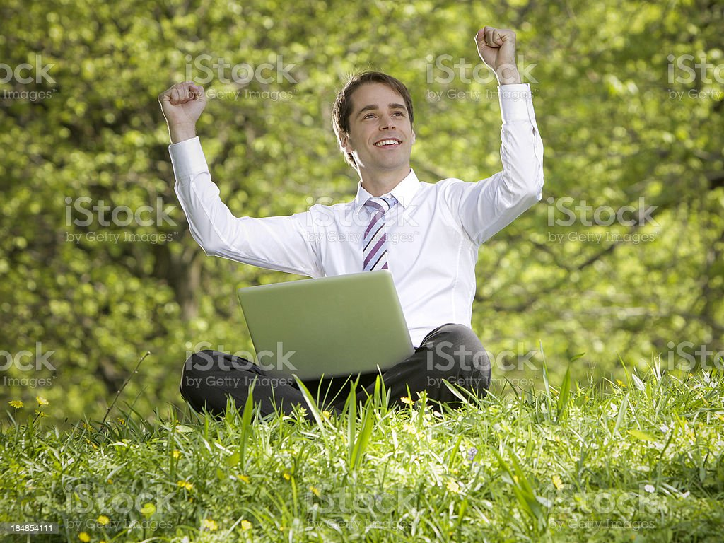 Young businessman sitting in the park with laptop royalty-free stock photo