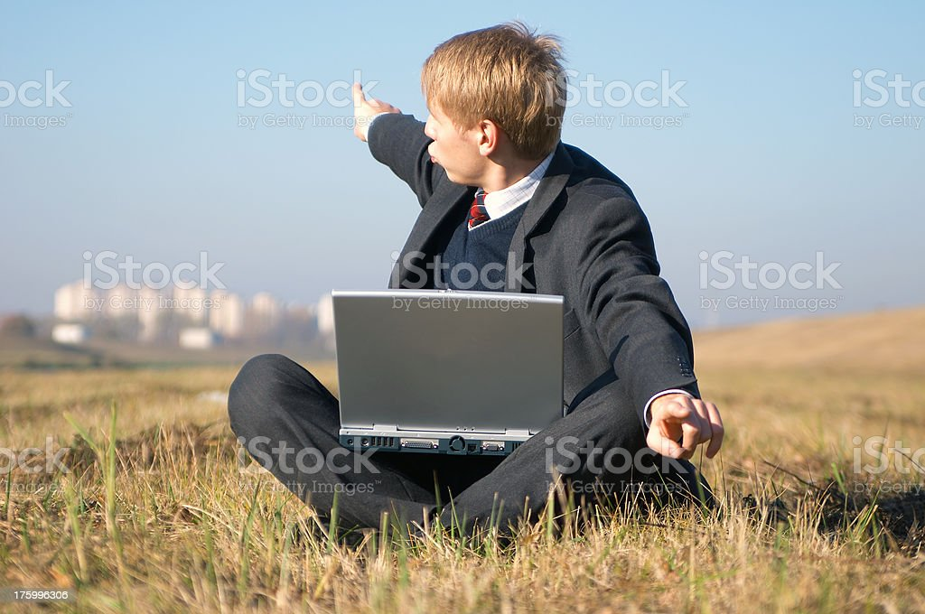 Young Businessman sitting on a grass stock photo
