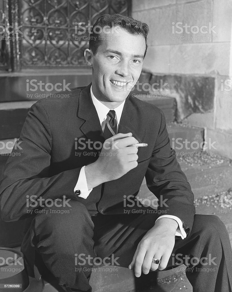 Young businessman sitting on steps, smoking cigarette, (B&W) stock photo