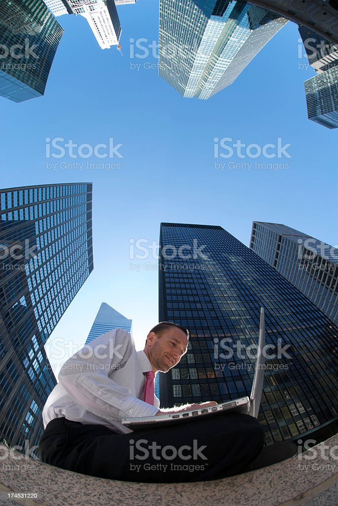 Young Businessman Sitting Using Computer Outdoors by Skyscrapers royalty-free stock photo