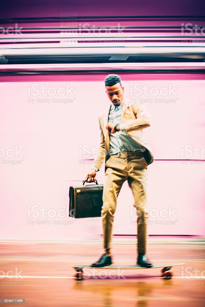 Young businessman skateboarding in offices stock photo