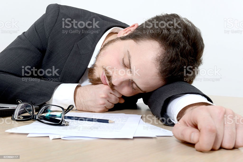 Young businessman sleeping on the office desk stock photo