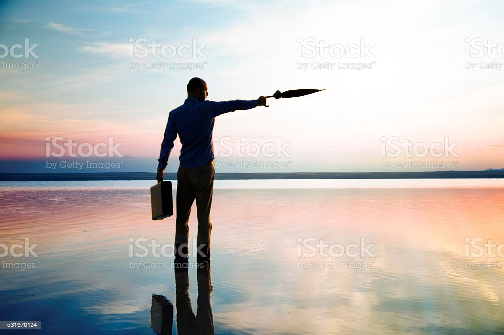 Young businessman standing against sunset. stock photo