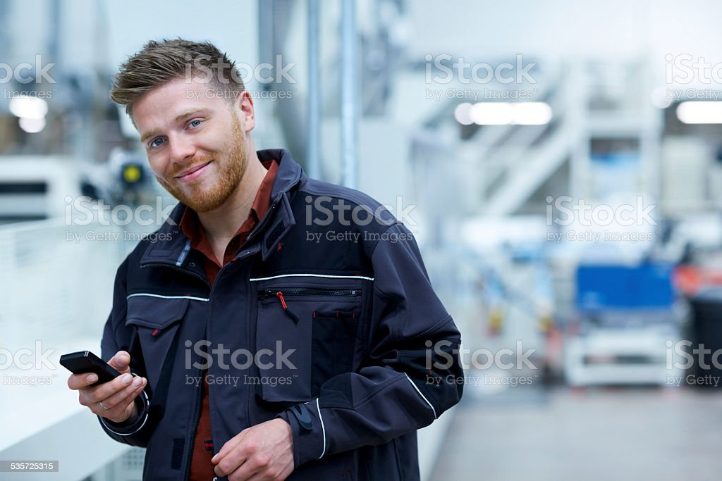 Young businessman standing in factory with a mobile phone stock photo