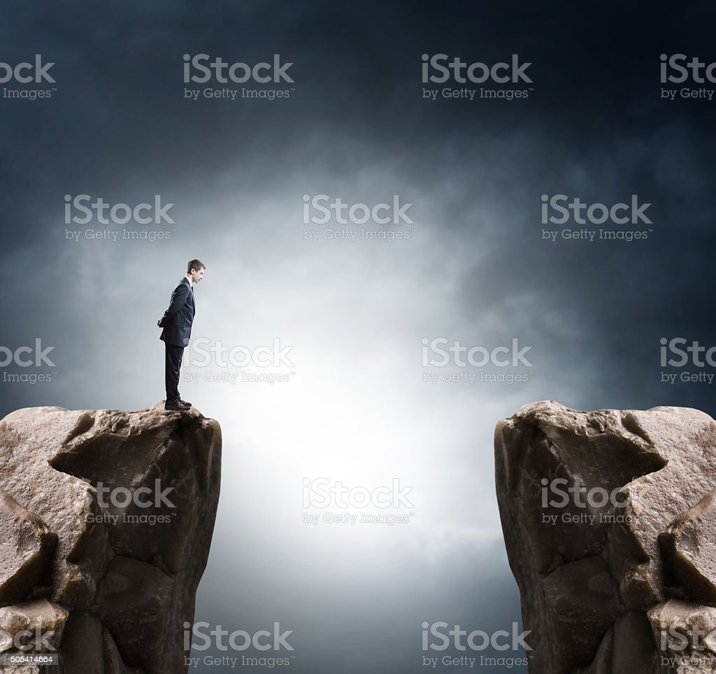 Young businessman standing on edge of rock mountain and looking stock photo