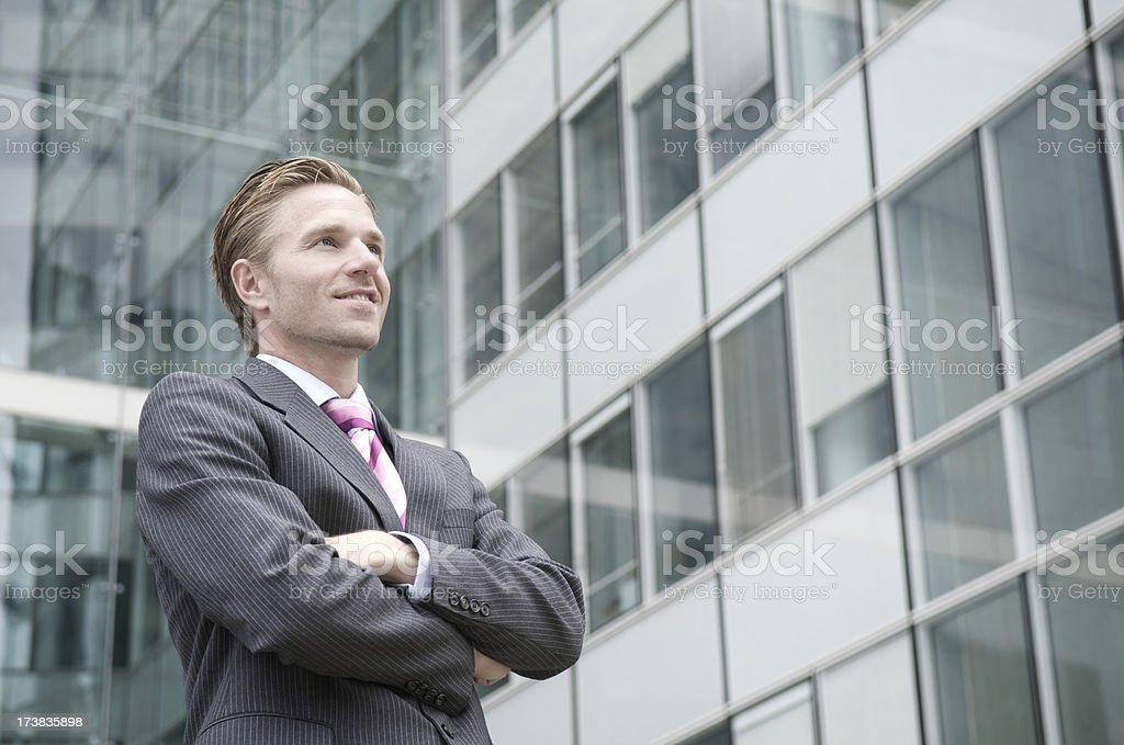 Young Businessman Standing Outdoors at Office Building with Arms Crossed royalty-free stock photo