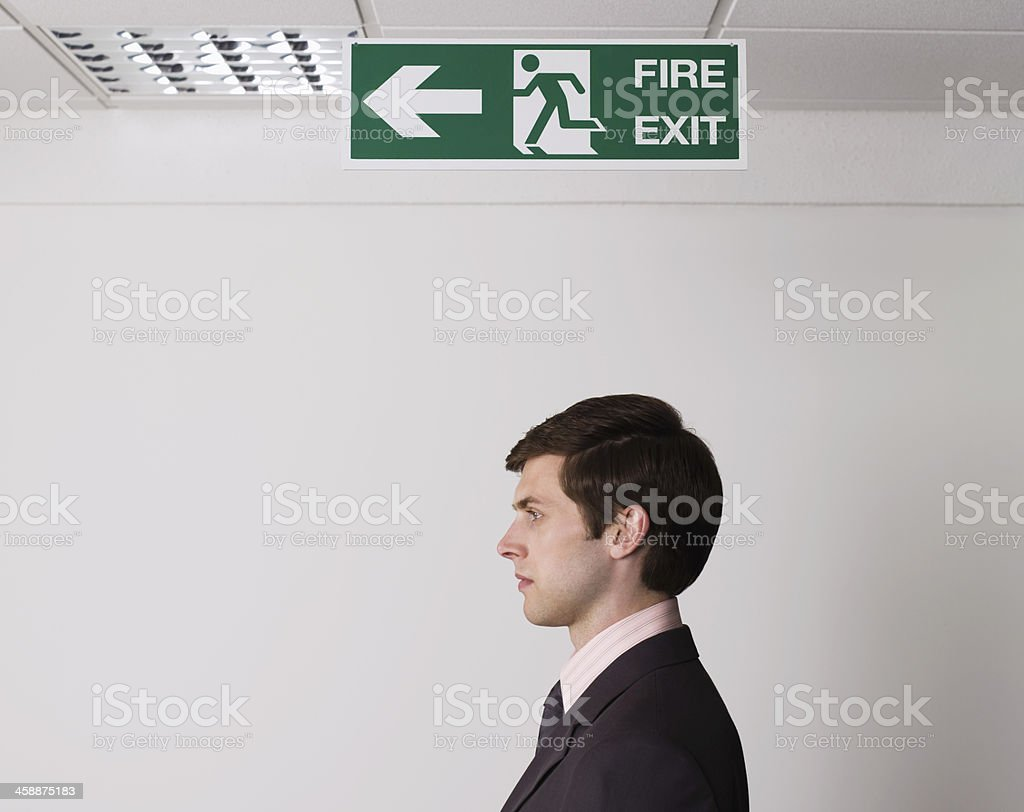 Young Businessman Standing Under Exit Sign stock photo