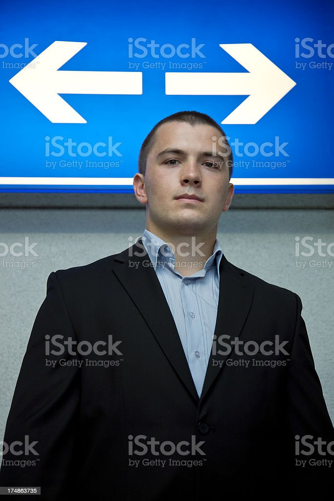 Young Businessman Standing Under Two Direction Arrow Sign, Concept Image royalty-free stock photo
