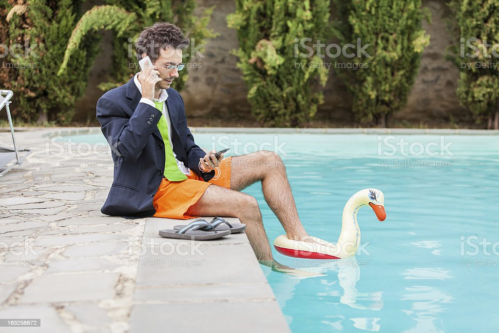 A young businessman taking a call by the pool royalty-free stock photo
