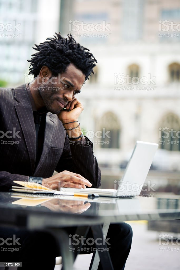 Young businessman talking on a cell phone while on a laptop. royalty-free stock photo