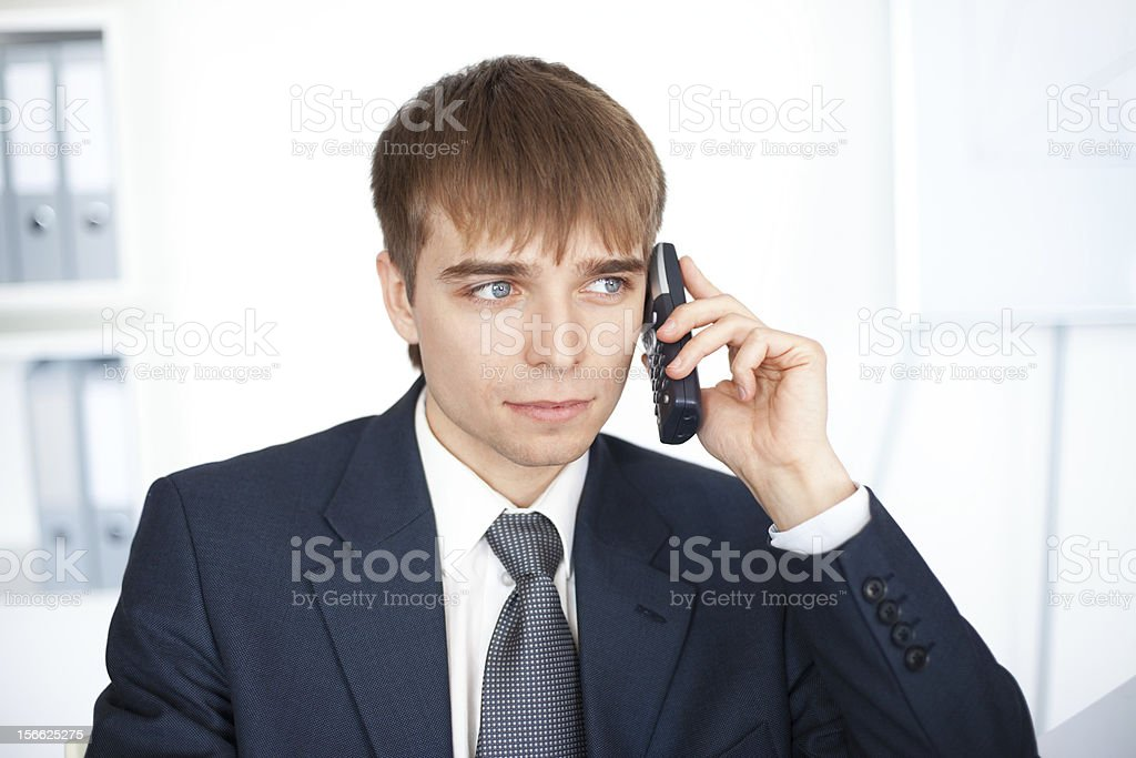 young businessman talking on cell phone in office royalty-free stock photo