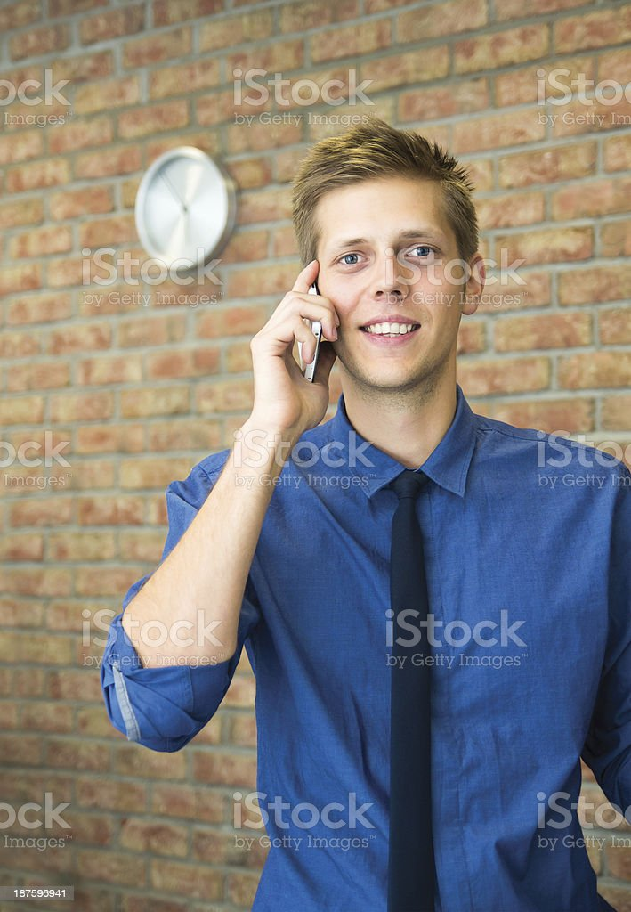 Young businessman talking on phone. Time concept in business royalty-free stock photo
