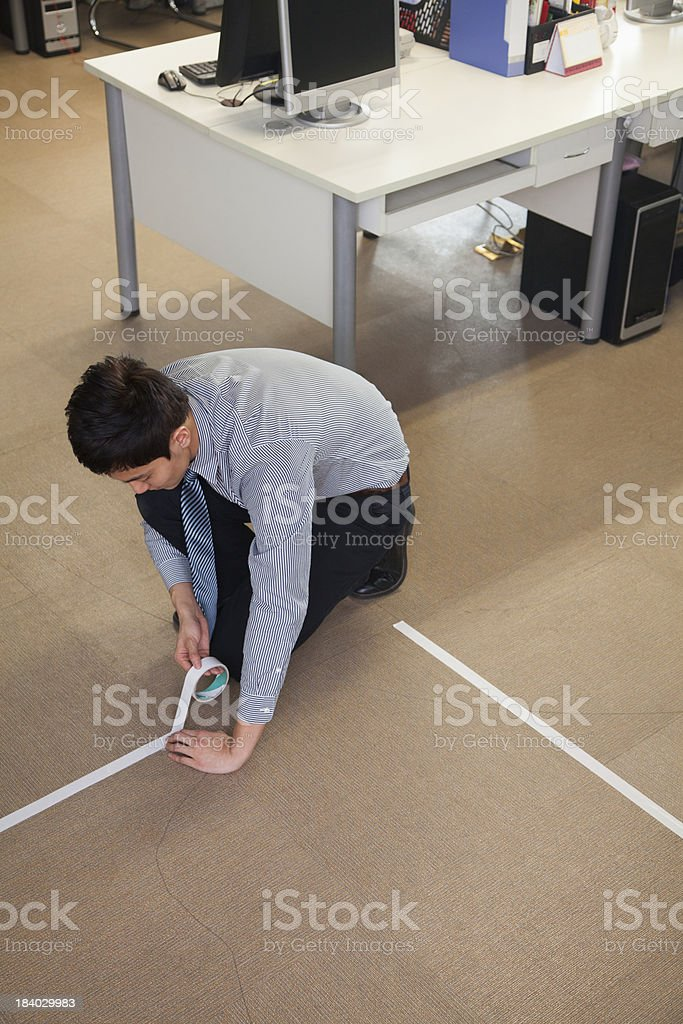 Young Businessman taping up the floor royalty-free stock photo