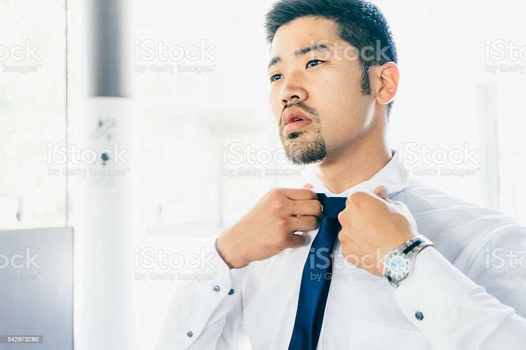 Young Businessman Tying His Tie stock photo