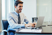 Young businessman typing on his laptop