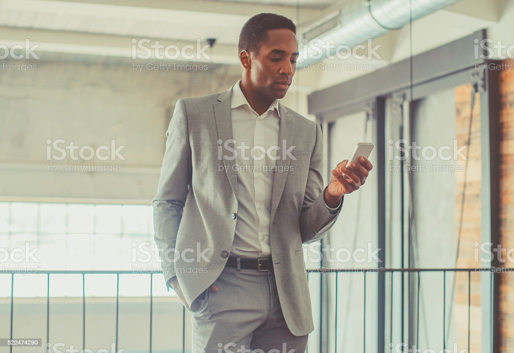 Young businessman typing on the smart phone stock photo