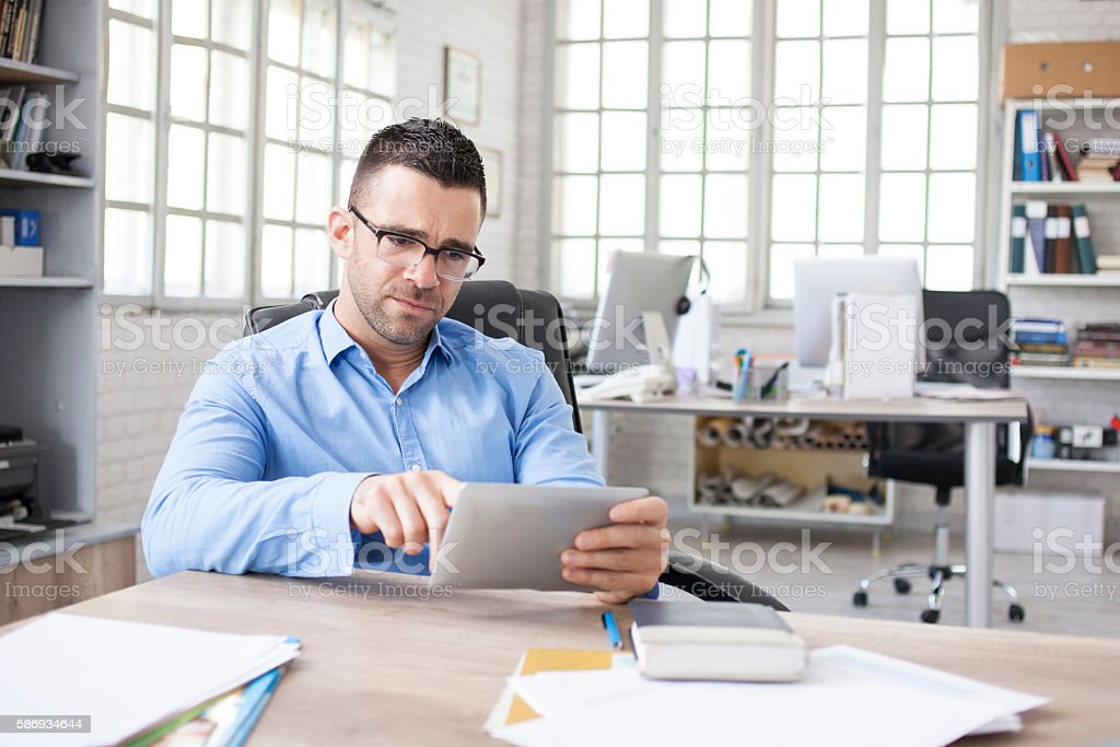 Young businessman using digital tablet at work stock photo