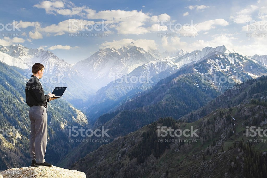 Young businessman using his laptop on the mountain top royalty-free stock photo