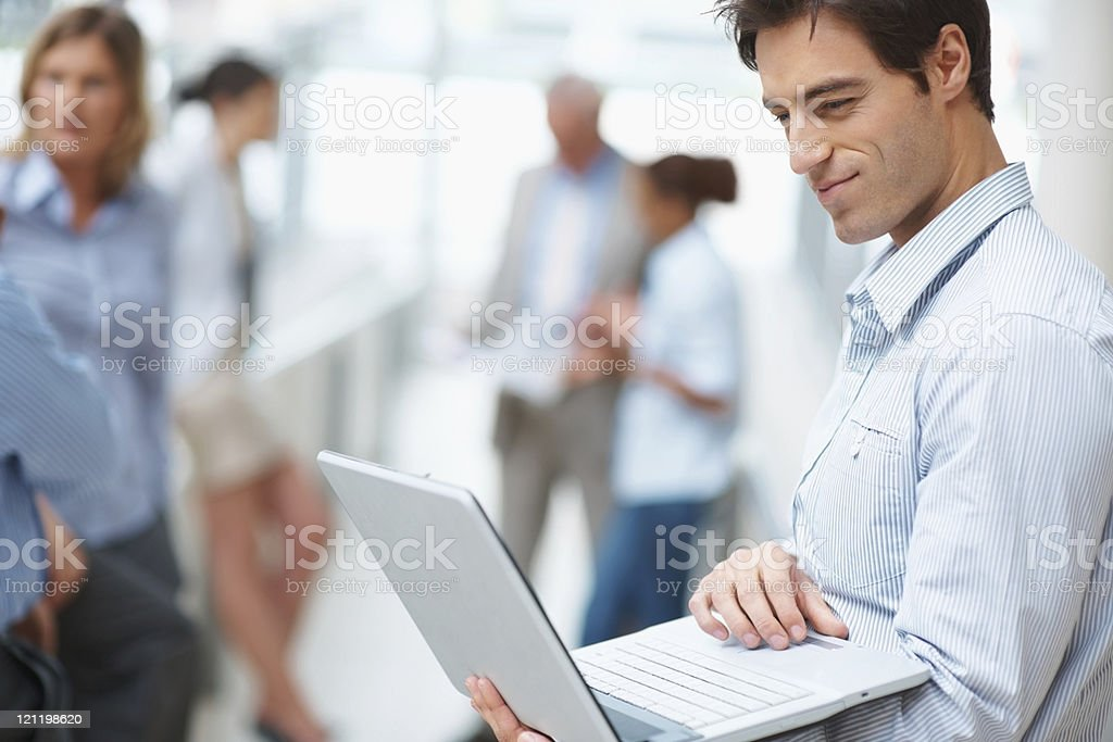 Young businessman using laptop with colleagues at the back royalty-free stock photo