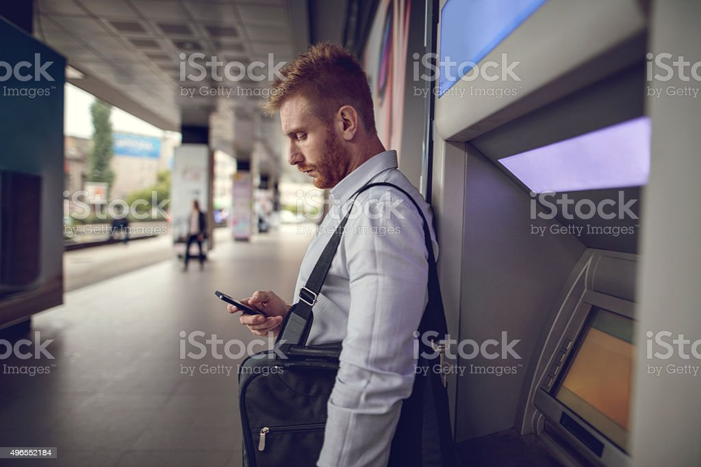 Young businessman using mobile phone next to a cash machine. stock photo