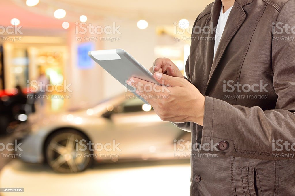 Young BusinessMan using Tablet device with Modern Sportcar stock photo