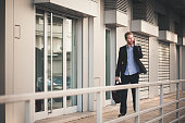 Young businessman walking and talking on the phone