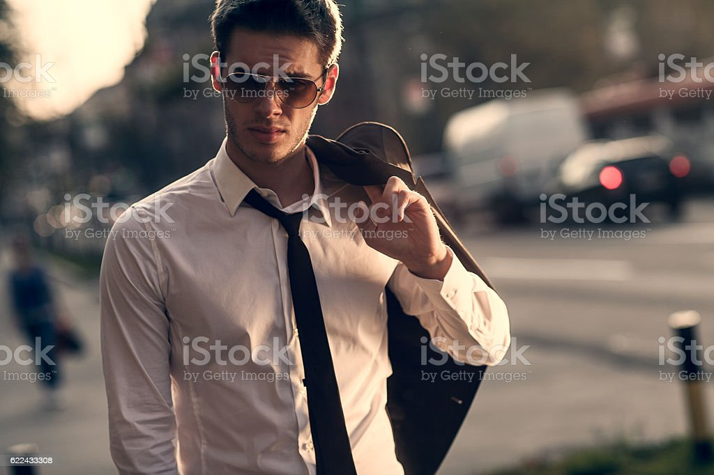 young businessman walking home after work stock photo