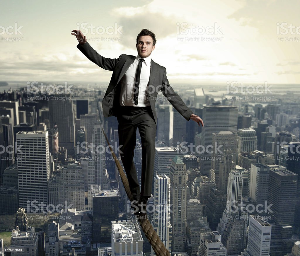 Young businessman walking on a rope between skyscrapers stock photo