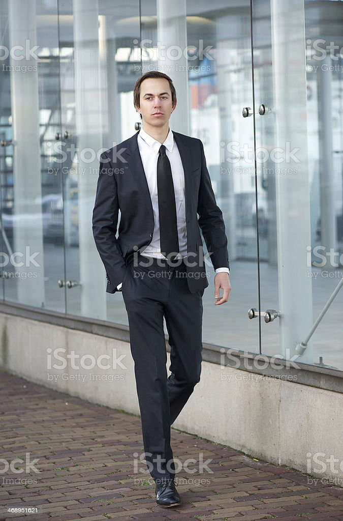 Young businessman walking on sidewalk in a suit royalty-free stock photo