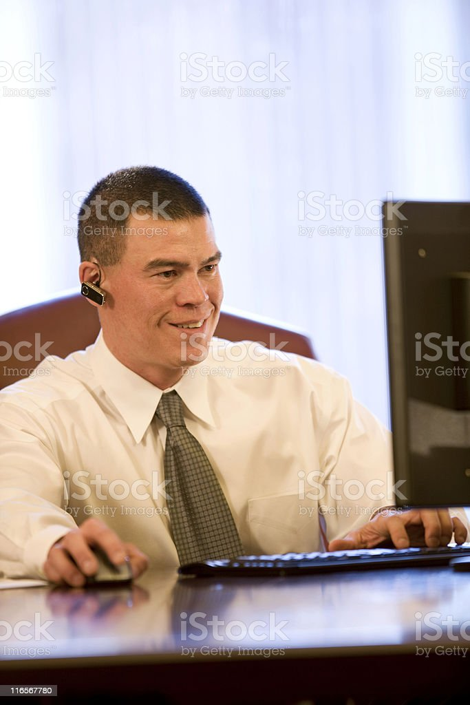 Young Businessman Wearing Bluetooth Working On Computer royalty-free stock photo