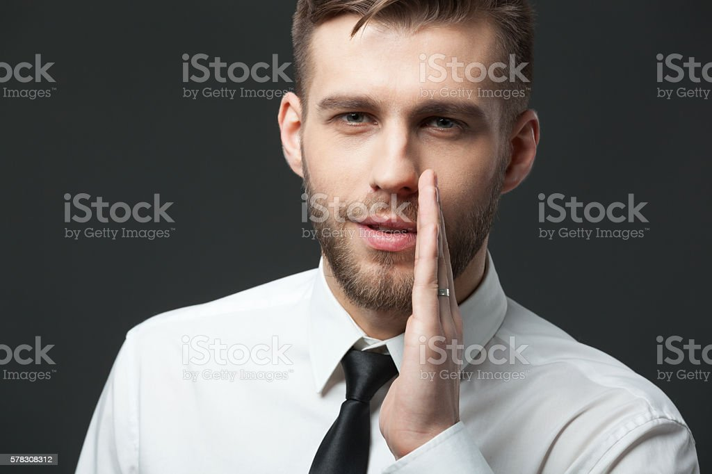 Young businessman whispering trade secrets on dark gray background. stock photo
